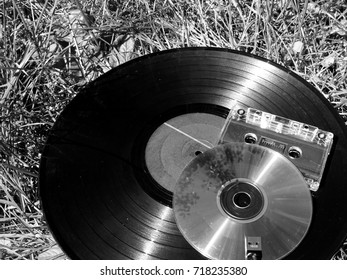 Vinyl record, CD, tape cassette and usb flash drive laying on the grass forgotten by time. Sound evolution concept.