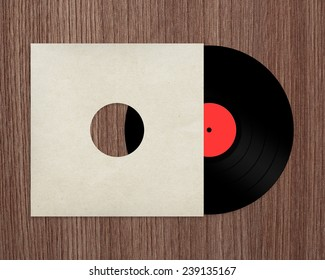 Vinyl record with cover on wooden table