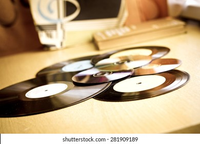 Vinyl record discs, CD and book on wooden table. Image with vintage filter