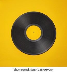 Vinyl record on a colored background. Old vintage vinyl record isolated on yellow background