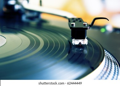 Vinyl record player for DJ. Turntable playing analog music records. Turntables needle in focus.Professional audio equipment for nightclub party and concert. Close up, pro equip
