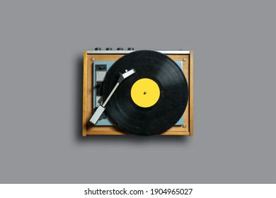 Vinyl record player with yellow label on a gray background. Modern phonograph record concept in trendy colors