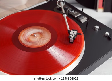 Vinyl record turntable rotate and black headphones on a white background. Equipment for the disc jockey. Sound technology for DJ to mix and play music. Red vinyl plate. Vinyl records with covers