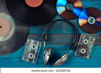 Vinyl records, CDs, audio cassettes, headphones are laid out on a blue wooden surface. Top view. 80s
