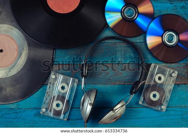 Des disques de vinyle, des CD, des cassettes audio, des écouteurs sont disposés sur une surface en bois bleu. Vue de dessus. années 80