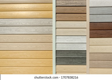 Vinyl siding with imitation wood texture in bright palette of colors. Plastic wall covering for exterior decoration of house. Abstract background for your design with copy space and place for text.