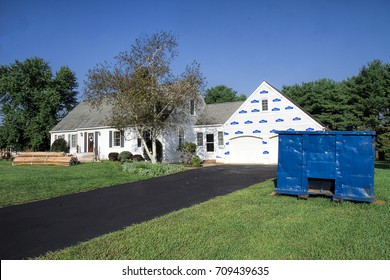 Vinyl Siding supplies packaged and sitting in front of home ready to replace existing siding on house.  Large commercial dumpster next to house ready for all debris and old siding to be placed.
