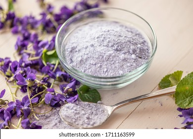 viola violeta odorata violet natural sugar bath salt on white background in porcelain dish  skin care product fragrant lilac soap, body oil, bath salts, tinctute, sirup used as cough remedy