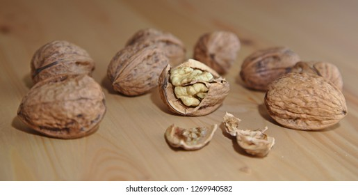 Violence. 1 cracked open walnut surround by 8 uncracked walnuts on a wooden surface.