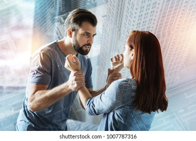 Violence. Furious cruel man painfully grasping the wrists of his scared young girlfriend and looking attentively at her