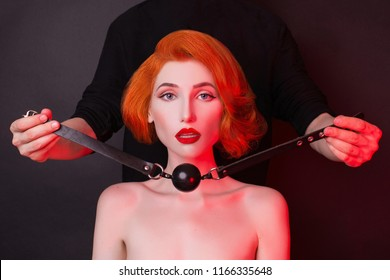 Violence in society. Redhead girl with gag on black background. Sexual bdsm toy. Attire for playing bdsm games. Woman violence. Photo in low key lighting. Black leather bondage with gag.