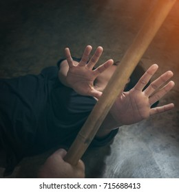 Violent man carries a wood stick and attempts to attack an scared woman that  fall down on the floor - concept photo of physical abuse