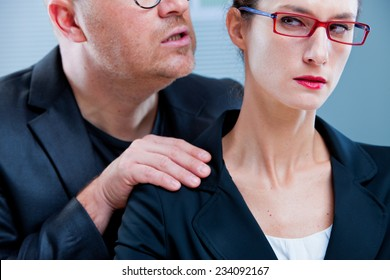violent man menacing an office worker woman maybe his colleague or subordinate