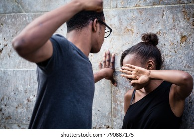 Violent young man threatening his girlfriend with his fist outdoors