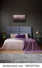 Violet blanket on bed with headboard in spacious bedroom interior with painting on grey wall