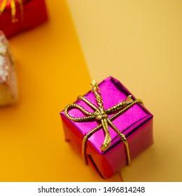 Violet box gift - Christmas tree toy lies on an orange background. Winter season. Web banner.