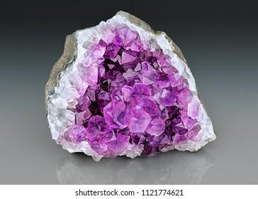 Violet Crystal Stone macro mineral. Purple rough Amethyst quartz crystals geode on gray gradient background, Uruguay