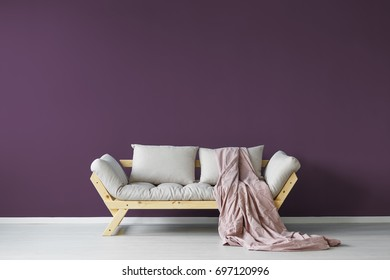 Violet day room interior with a cozy couch and a claret blanket
