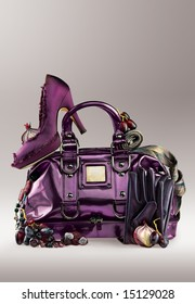 Violet elegance. Violet shoe on a purse with jewelry and gloves.