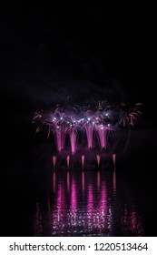 Violet fountain and blue willows in rich fireworks over Brno's Dam with lake reflection