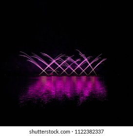 Violet fountain fireworks over Brno's Dam with great lake reflection