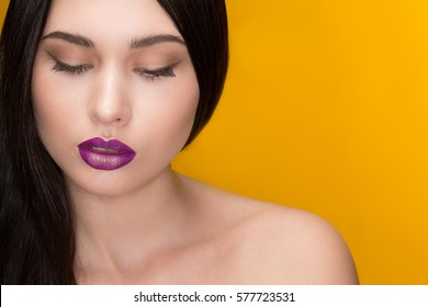 Violet and gold. Close up of a beautiful young dark haired young female model posing with her eyes closed wearing creative gold and purple makeup sensual sexy seductive lipstick makeup yellow concept