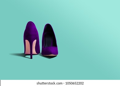 Violet high heels footwear on an isolated green pastel background. Fashion concept, catwalk. Online store, fashion store, sale of shoes. The high heel lies next to the other. Close up. Female shoes.