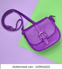 Violet leather bag on a colored pastel background. Minimalism, top view