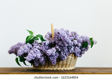 Violet lilac flowers bunch in a basket on wooden table