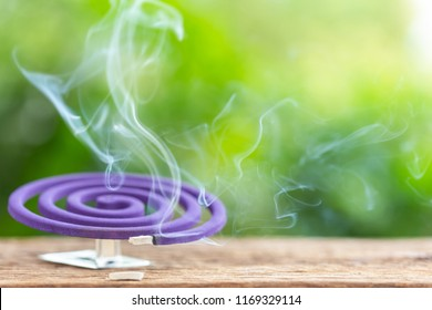 Violet mosquito repellent and white smoke on wooden table with green blur light space background for text, design, photo montage or advertising