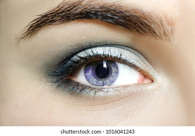 Violet mutation eyes , Close Up. The human eye of a woman with light beauty cosmetics and long natural eyelashes. Girl with perfect skin