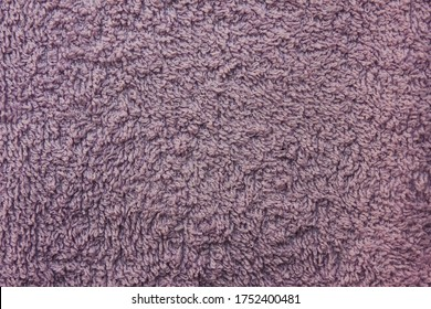 Violet old terry cloth texture background. Pale purple color terry cotton towel close up view. Household bath towelling cloth, used towel closeup texture