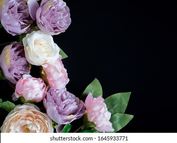 Violet, pink and white flowers arranged on a dark background. Bridal theme. Wedding anniversary or invitation idea. Top view. Flat lay. Insert your own text.