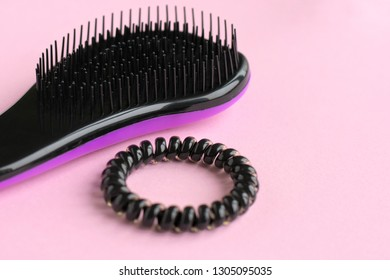 violet plastic hair comb with black bristles with selective focus and blurred spiral black scrunchies on neutral pink background. Hairbrush with elastic scrunchy for female hairstyle