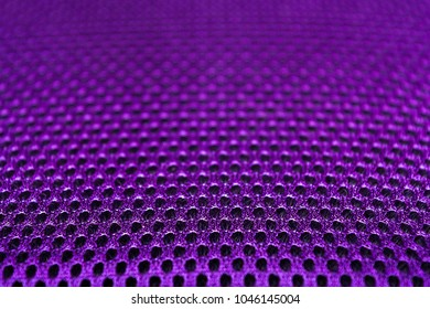 Violet Polyester texture. The breathable material. The holes for air. The back of the backpack. Blurred background. Space for text.
