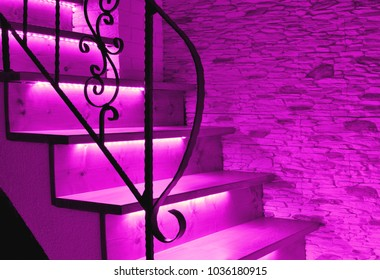 Violet, purple LED lighting wooden stairs with antique railing