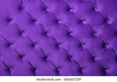 Violet purple velvet capitone textile background, retro Chesterfield style checkered soft tufted fabric furniture diamond pattern decoration with buttons, close up