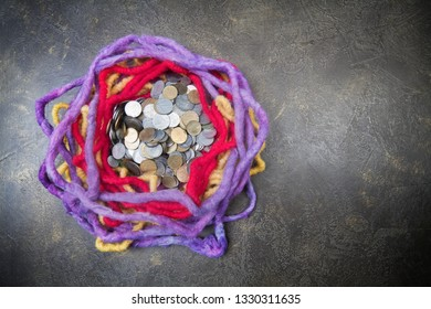 Violet, red and yellow woolen nest  on dark background, with space for your logo or text and coins