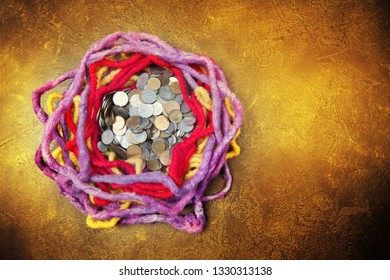 Violet, red and yellow woolen nest  on dark and golden background, with space for your logo or text and coins