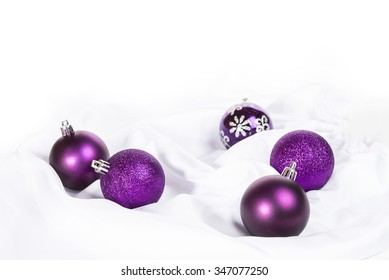 violet and silver Christmas balls on a white table