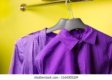 violet  women's dress and violet  men's shirt on the hanger, bright holiday clothes for couple, bright yellow background