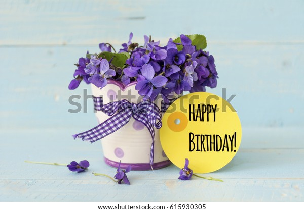 violets flowers in a blue vase with happy birthday message