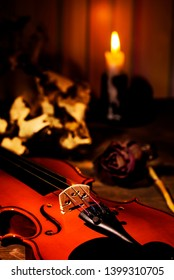Violin and autumn leaves on the on the table in light of candle in the dark room. Close-up of violin. Focus on the strings.