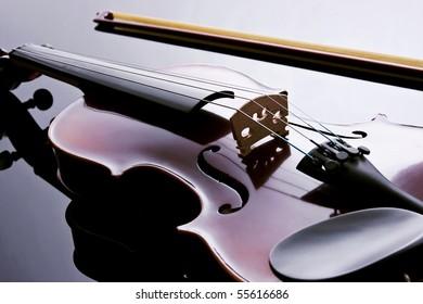 Violin in backlight over black acrylic. Studio photography.
