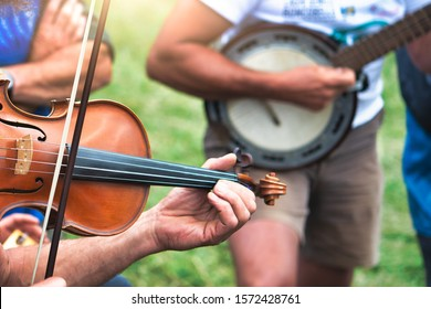 Violin and banjo played outdoors in a popular country party