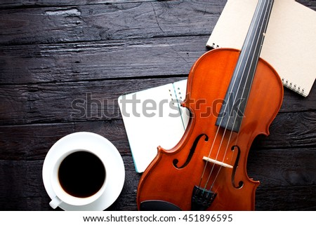 violin and book on wooden table and coffee cup