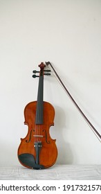 A violin and bow against the wall, string instrument on white background