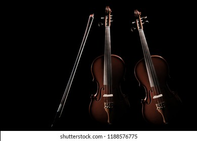 Violin with bow. Classical orchestra music instruments. Two violin isolated on black background