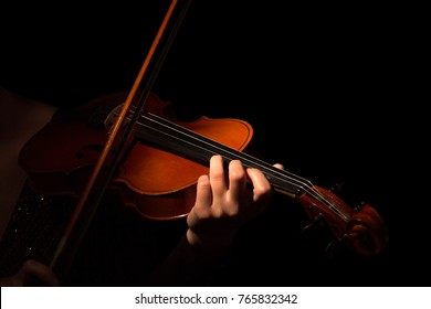 Violin and bow in the hands of musician isolated on black background