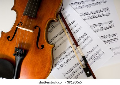 A violin and bow lying on sheet music